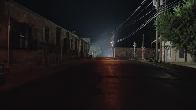 wide angle of small town street in back of building in industrial area  near railroad track crossing. brick buildings visible. power or electric lines visible. - industrial district stock videos & royalty-free footage