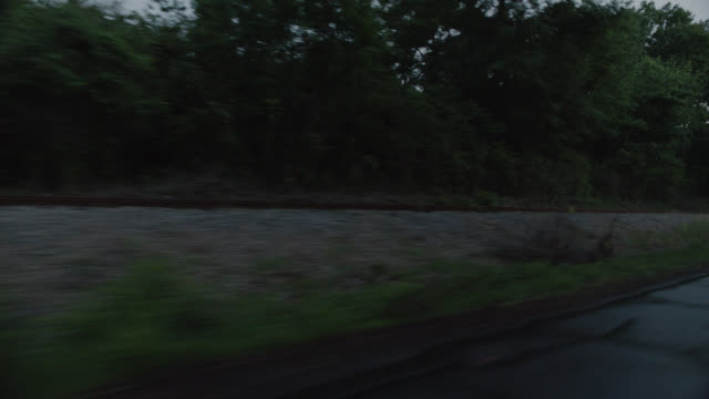 process plate 3/4 back right of railroad tracks in rural area. wet road. trees visible. cars swerve to avoid camera. could be car chase. car stunts. - wet wet wet stock videos & royalty-free footage