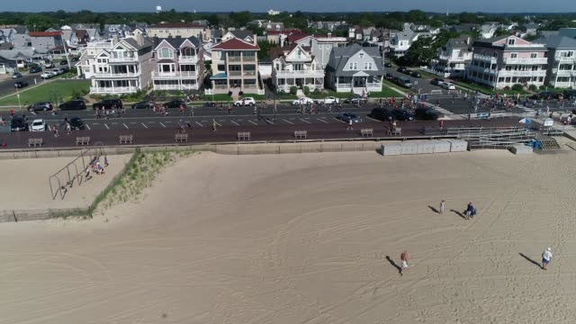 drone running race adjacent to ocean and beach camera moves from ocean to race in progress - salmini stock videos and b-roll footage