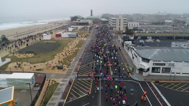 vidéos et rushes de drone - running race adjacent to ocean and beach - salmini