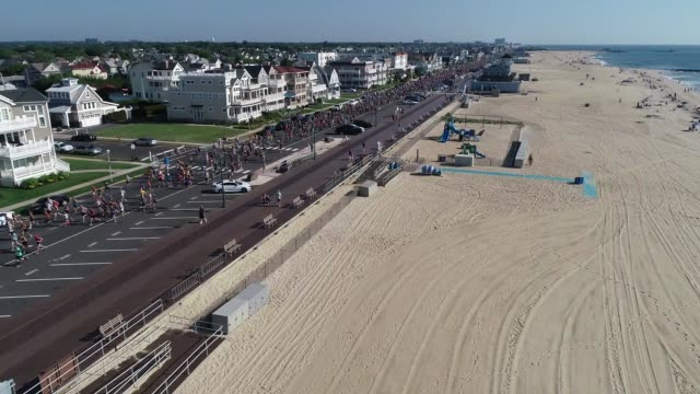 drone running race adjacent to ocean and beach - salmini stock videos and b-roll footage