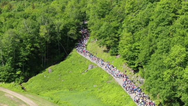 vidéos et rushes de drone - runners head into tree cover going up mountain - salmini