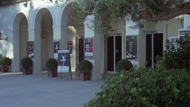 zoom in on sign with picture of ballerina in front of the wilshire ebell theatre with arches above entrance. could be playhouse. - wilshire ebell theatre stock videos & royalty-free footage