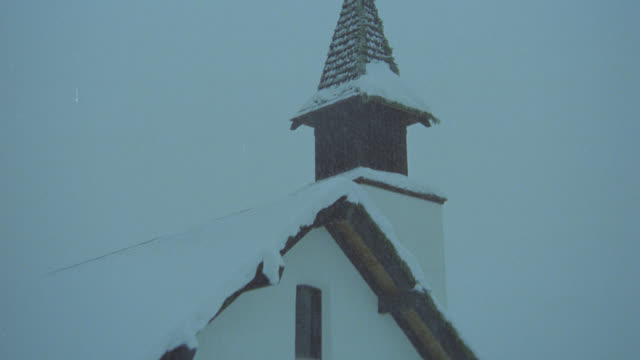pull back from snow falling on top of steeple to church show one story church building with cars parked in front. snow. - steeple stock videos & royalty-free footage