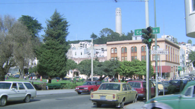 pan right to left from coit tower in bg and cars driving on street in fg to saints peter and paul church with ornate steeples in north beach. people walking in washington square park in fg. could be small town. - coit tower stock videos & royalty-free footage