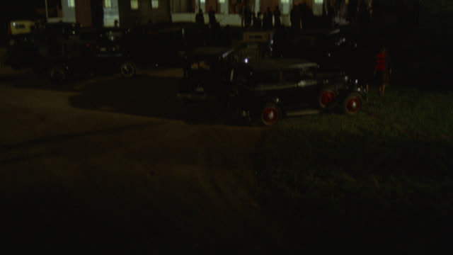 pan up of cars parked in front of two story upper class house. people standing on porch and walking toward entrance. could be party. - zweistöckiges wohnhaus stock-videos und b-roll-filmmaterial