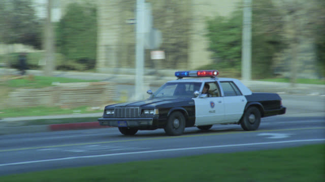 wide angle of police cars with bizbars, flashing lights speeding down city street. police cars turn left into driveway of multi-story building, could be government building or church. - 1985 stock-videos und b-roll-filmmaterial