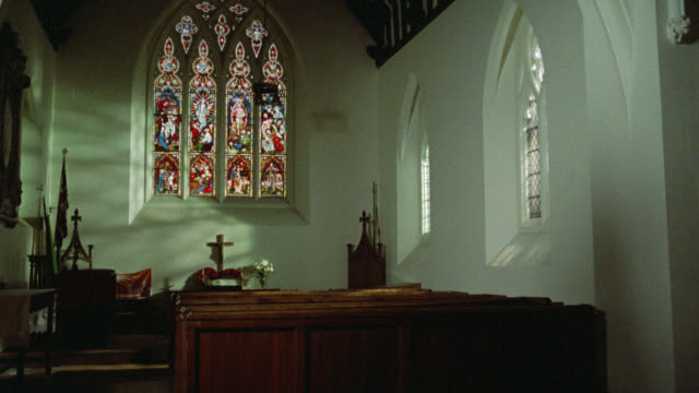 medium angle of church pews, alter and stained class window in small church. crosses. - altare video stock e b–roll