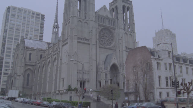 zoom in on entrance to ornate grace cathedral on street corner in san francisco. gothic cathedrals. cars driving by in fg. - tornspira bildbanksvideor och videomaterial från bakom kulisserna
