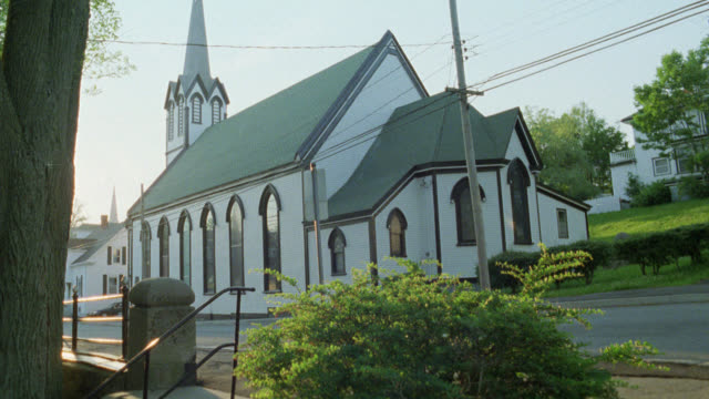 wide angle of small white church with steeple. could be in small town. - steeple stock videos & royalty-free footage