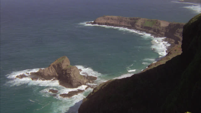high down from top of cliffs of waves crashing against rocky coastline, cove. oceans. could be tropical location. - insel kauai stock-videos und b-roll-filmmaterial