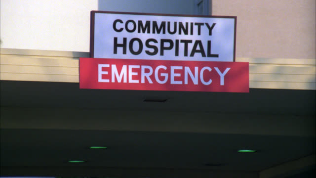 pull back from sign for community hospital emergency to show police cars parked in front of building. could be medical center. - building entrance stock videos & royalty-free footage