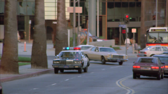 pan right to left as police car with flashing lights or bizbar and brown coupe car speed around street corner. city street. cars park outside of  apartment building or condominium. could be hotel. - blaulicht stock-videos und b-roll-filmmaterial