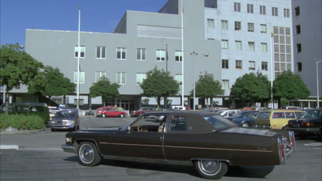 wide angle of brown car parked in fg of parking lot. multi story building in bg. could be office building, federal agency or administration building, or hospital or medical center. police officer on motorcycle - キャデラック点の映像素材/bロール