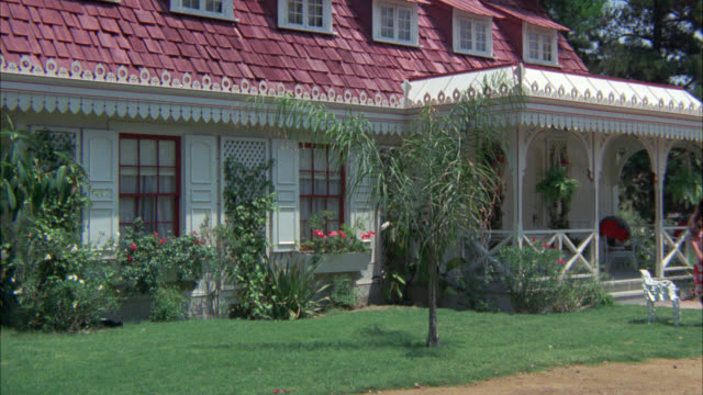 wide angle est fantasy island guest house which is a white two story victorian with shingled roof.  covered front porch.  two women in hawaiian-print dresses walk by r-l. tropical palm trees. - zweistöckiges wohnhaus stock-videos und b-roll-filmmaterial