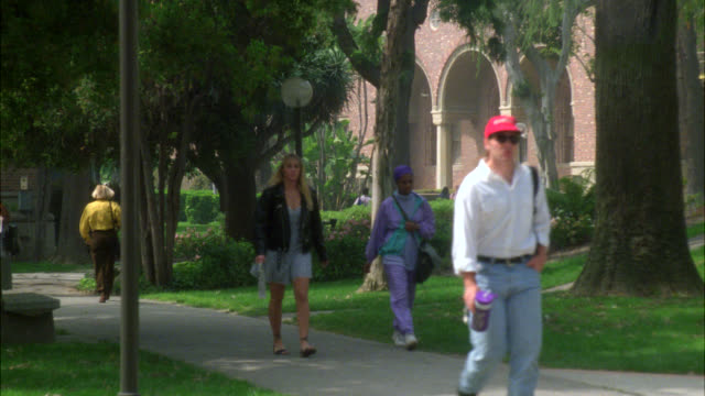 wide angle of students, people walking on sidewalk on college, university or ivy league campus. grass, trees and multi-story brick buildings. usc campus. - 1993年点の映像素材/bロール