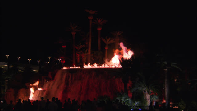 wide angle of people gathered, watching the volcano erupting with fire and lights in front of the mirage hotel. hotels. crowds. las vegas strip. - the mirage las vegas stock videos & royalty-free footage