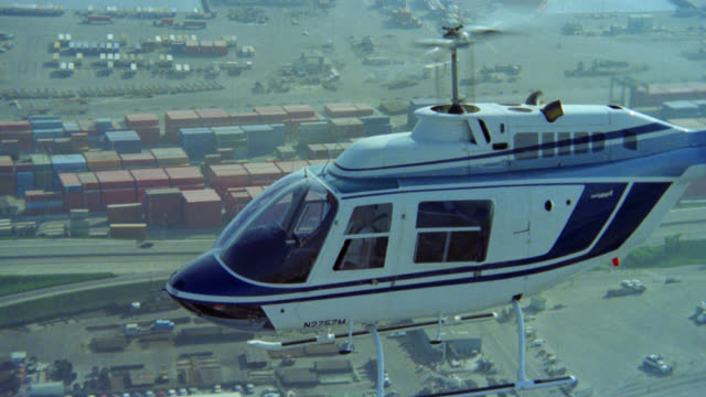 aerial of helicopter over los angeles freeways highways waterfront downtown long beach. shot traveling alongside helicopter as it flies over city long beach (same shot at r15-5). action. - 1985 stock videos & royalty-free footage