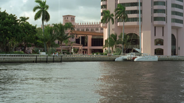 vidéos et rushes de wide angle of catamaran docked on waterway in front of multi-story building, could be upper class hotel, resort or apartment building on waterway. tropical. - stéréotype de la classe supérieure