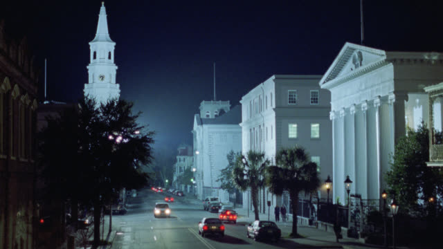 """pan down from cars driving on street in city or small town past church with steeple and a building with columns to upper class hotel with awning over sidewalk that reads """"mills house hotel"""" people walking on sidewalk past hotel and door man carries bags o - steeple stock videos & royalty-free footage"""