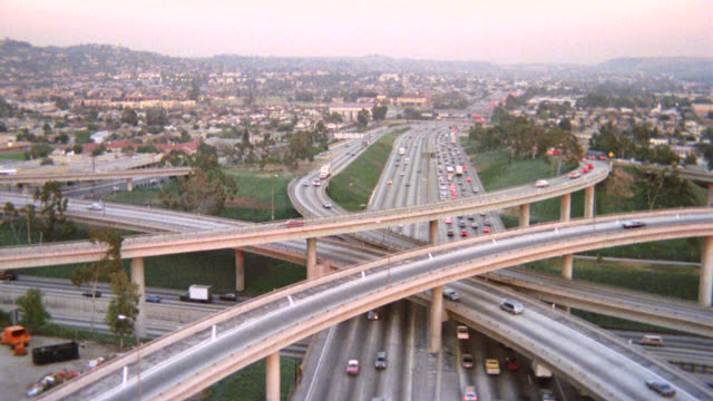 aerial over los angeles freeways or highways, over off ramps and on ramps until closer on dead body of woman on grass next to freeway on ramp. surveillance camera. corpse. crime scene. hazy or smoggy sky. - motorway junction stock videos & royalty-free footage