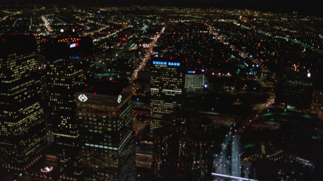 aerial of los angeles city skyline  at night. pov flies around downtown high rises. see freeways with traffic below. - 1987 bildbanksvideor och videomaterial från bakom kulisserna