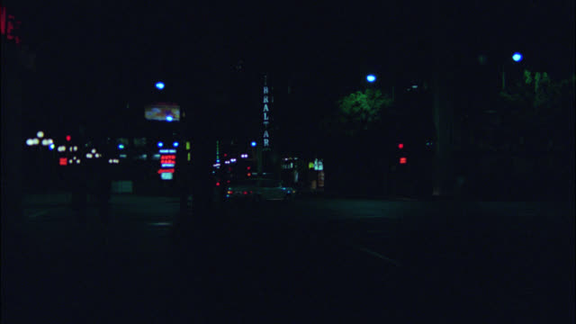 pan up from city street with neon signs to high rise office building. windows with lights. could be downtown. - 1980 stock videos & royalty-free footage