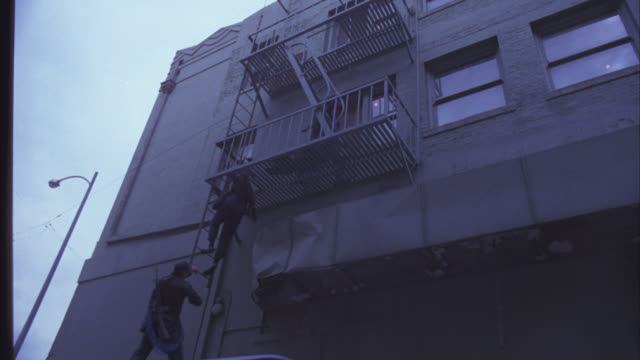 up angle of swat team climbing fire escape on back of apartment building. windows and roof visible. air duct. van visible parked in alley. urban area. - fire escape stock videos & royalty-free footage
