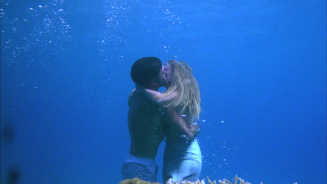 camera moves up and over black haired man kissing blonde mermaid with blue fin underwater - hawaii islands stock videos & royalty-free footage