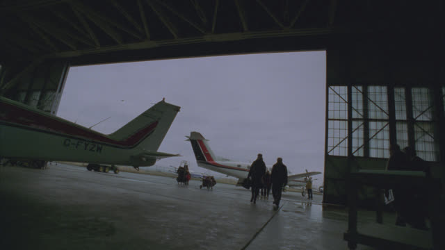 wide angle of small airport hangar. airplanes parked on tarmac. people or travelers. - 飛行機格納庫点の映像素材/bロール