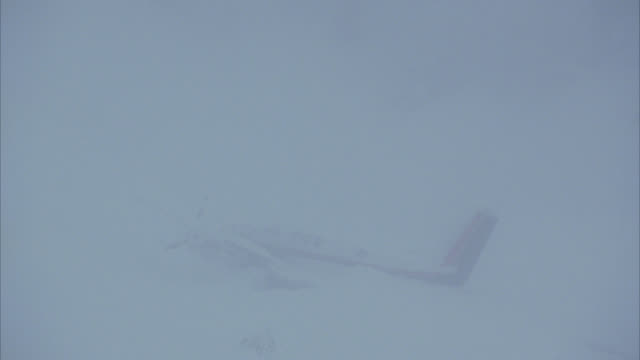 MEDIUM ANGLE OF TWIN ENGINE, WHITE CESSNA AIRPLANE CRASH SITE IN SNOW. COULD BE PRIVATE OR CORPORATE JET OR AIRPLANE. SEE FUSELAGE AND TAIL STICKING OUT OF SNOW. SEE RED COLOR ON TAIL. ACTION.