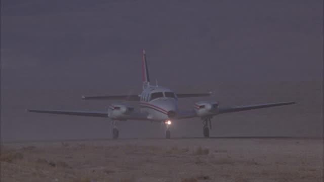 pan left to right of twin prop airplane taking off on desert airstrip made of dirt. - flygfält bildbanksvideor och videomaterial från bakom kulisserna