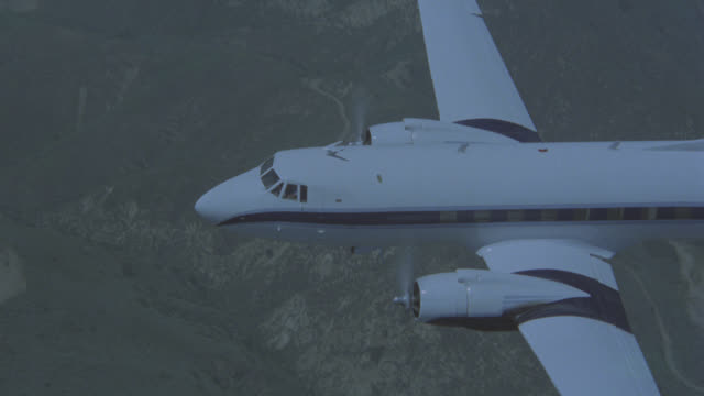 aerial air-to-air tracking shot of all white with  blue stripe twin engine propeller commuter jet or airplane flying over mountains and valley. could be dc-3 airplane. see clear blue sky and rural area with green trees and vegetation below. - air to air shot stock videos & royalty-free footage