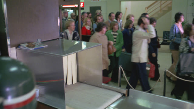 wide angle of people running past armed soldiers through airport security check, x-ray machine. could be emergency or evacuation. crowds. panic. - evacuazione video stock e b–roll
