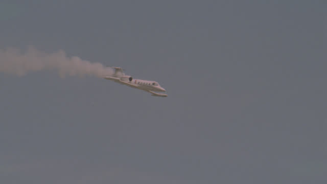 vídeos de stock e filmes b-roll de wide angle of lear jet, airplane, private jet or corporate jet with smoke coming from back end flying through the sky. airplane crashes. - acidente de avião