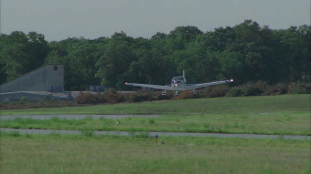 up angle of small single-propeller plane landing on rural area runway. plane touches down and takes-off again. piper saratoga plane. trees surround airfield. - propeller video stock e b–roll