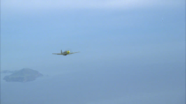vidéos et rushes de aerial of single-engine airplane or  military airplane flying over mountains or islands. could be hawaii or tropical island. clouds. could be air force plane. plains on island visible. water or ocean visible. - angle de prise de vue
