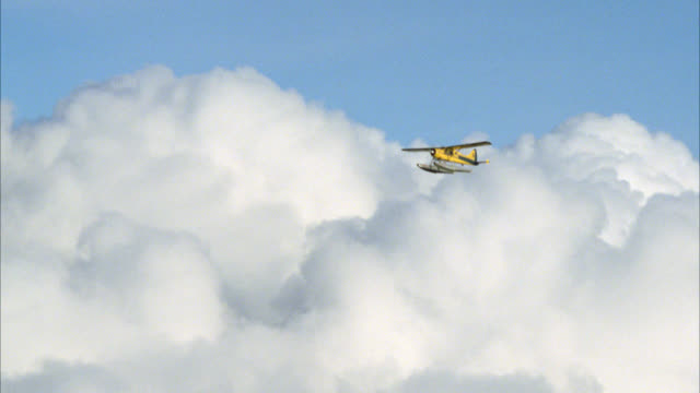 aerial plane-to-plane tracking shot of yellow seaplane or airplane flying above white puffy or cumulus clouds in the blue sky. - 積雲点の映像素材/bロール