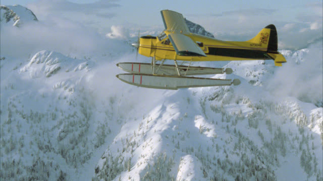 vídeos de stock e filmes b-roll de aerial plane-to-plane tracking shot of yellow seaplane or airplane flying above snow covered mountains with pine trees in bg. in forest. - pine