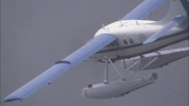 medium angle of blue and white single engine seaplane or airplane flying through thick layer of fog, mist, or clouds in sky. - 水上飛行機点の映像素材/bロール
