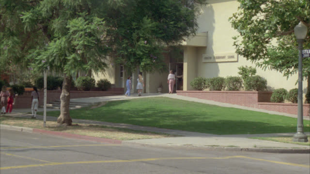 "vidéos et rushes de wide angle of students walking toward and entering two story elementary school building with sign reading ""addison elementary school"" on side of building. students walking across the street and cars driving through intersection. - school building"