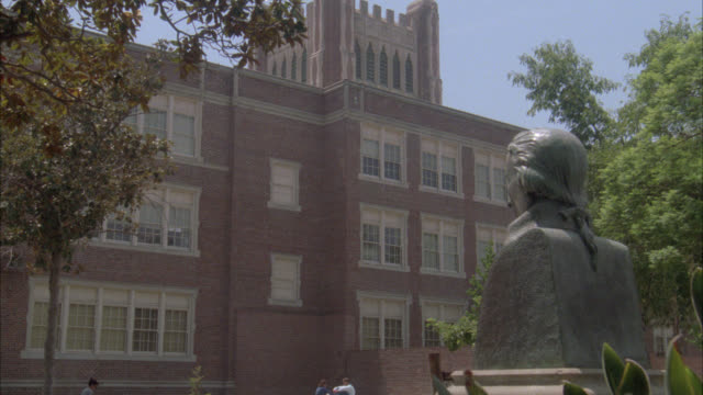 wide angle of people, students walking past three story brick building, could be high school or college or university. back of bust sculpture in fg. - bust sculpture stock videos and b-roll footage