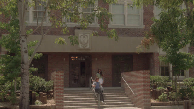 wide angle of entrance of multi-story brick building, could be high school or middle school. students, teenagers and woman, could be teacher, exit building and walk down steps. teenagers riding by on bikes. - 高等学校点の映像素材/bロール