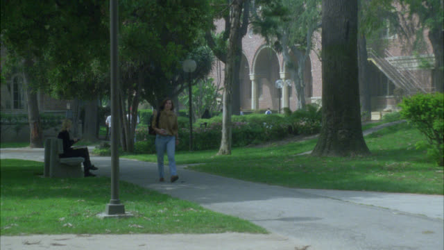 wide angle of students, people walking on sidewalk on college, university or ivy league campus. grass, trees and multi-story brick buildings. usc campus. - 1993点の映像素材/bロール