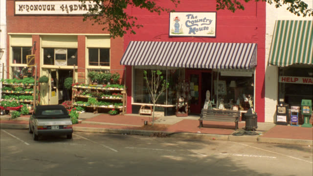 stockvideo's en b-roll-footage met pan right to left of cars driving past shops with awnings in small town, downtown. main street. - straatnaambord