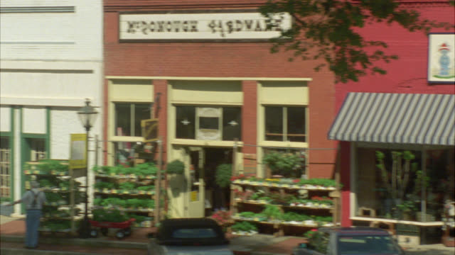 """stockvideo's en b-roll-footage met pan right to left from shops with awnings in small town, downtown to entrance of three story brick building.  could be private school, academy, middle school or high school. sign above entrance reads """"welcome back rawley students."""" main street. - straatnaambord"""