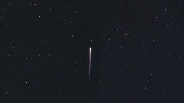 wide angle of comet, fireball or spaceship moving through sky. stars. outer space. clouds. comet switches from night to day. asteroid. - fireball stock videos & royalty-free footage