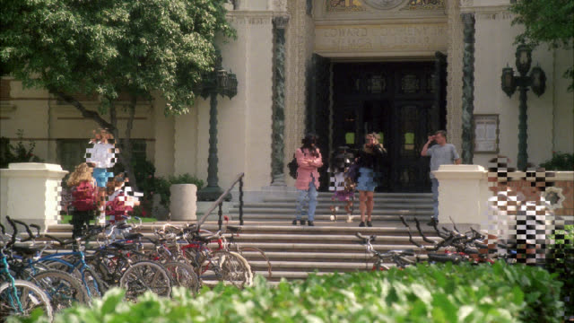 wide angle of main entrance to doheny library at usc. college campus,  university. could be used for lecture hall or classroom building. students enter exit. students wear short pants, t-shirts, carry backpacks, could be  summer school. bicycles and bushe - 1993 stock videos & royalty-free footage
