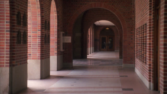 wide angle of covered walkway or exterior hallway at university college campus. red brick building with arches, lecture hall, auditorium or library. students walk by. young man on skateboard rolls by. usc campus. - 1993 stock videos & royalty-free footage