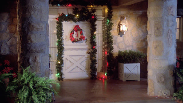 medium angle of ranch style house with christmas decorations. wreath and garland on front door with twinkling christmas lights. festive. upper class. pillars or columns at entrance. - ranch house stock videos & royalty-free footage